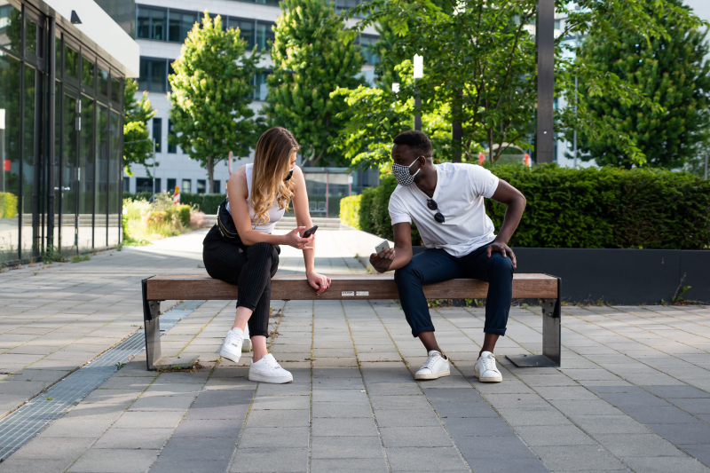 Ey-young-man-and-woman-social-distancing-on-bench-using-phones